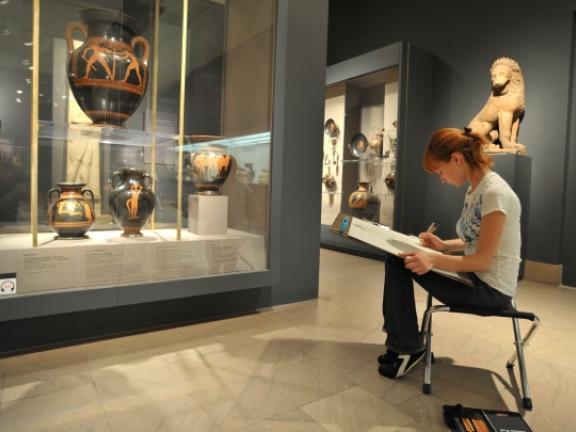 Girl drawing Greek vases on drawing pad in Greek gallery