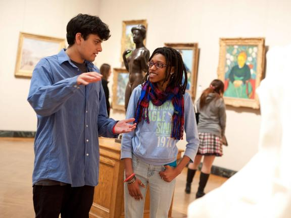 Two young visitos chatting in old Impressionism gallery