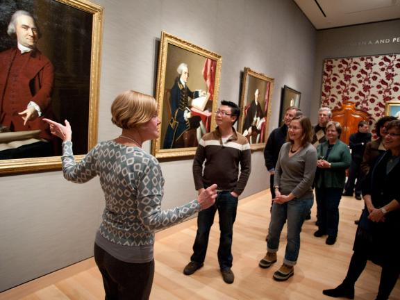 Guide pointing to Samuel Adams portrait with tour group in Revolutionary Boston gallery