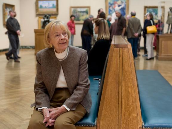 Woman sitting on bench in impressionism gallery