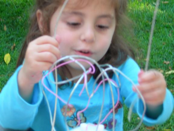 Young girl making sculpture with wires outside