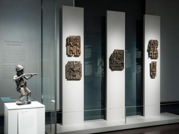 View of Art of Benin Kingdom gallery, with bronze sculpture of soldier holding rifle in foreground and bronze plaques on wall in background