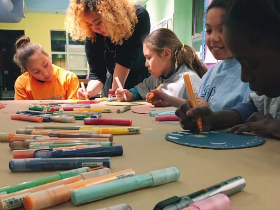 Kids sitting around table working on art project with markers, guided by teacher