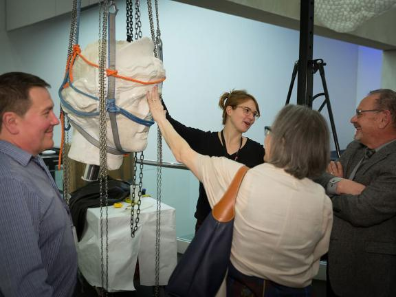 Visitor touching head of Juno statue suspended on pulley system