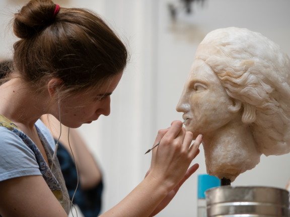 Teen using tool on bust of head