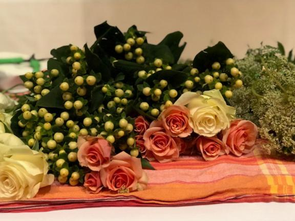 Pink roses and green berries on tablecloth