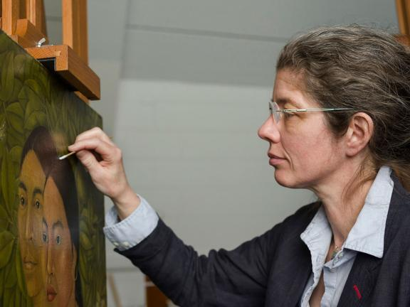 Conservator holding brush, working on Frida Kahlo's painting, Dos Mujeres