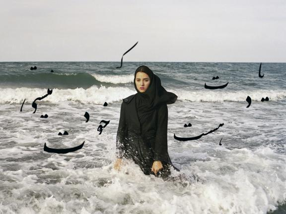 Photograph of woman standing in waves, with Arabic letters printed around her