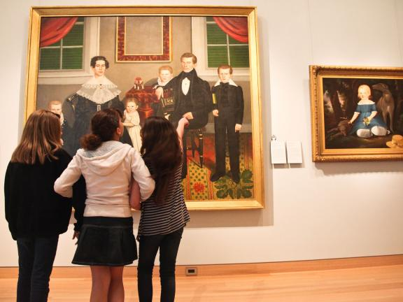 Three young visitors looking at painting in Folk Art Gallery