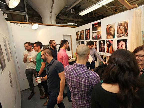 Visitors looking at artwork hanging on walls of SMFA graduate student studios