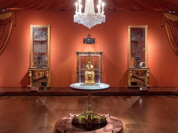 View of English Regency gallery, with round table in foreground and chandelier above