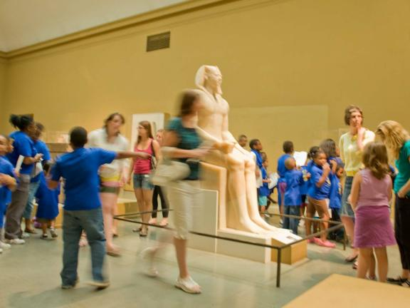 Group of kids in blue shirts in Egyptian gallery during Free Fun Friday
