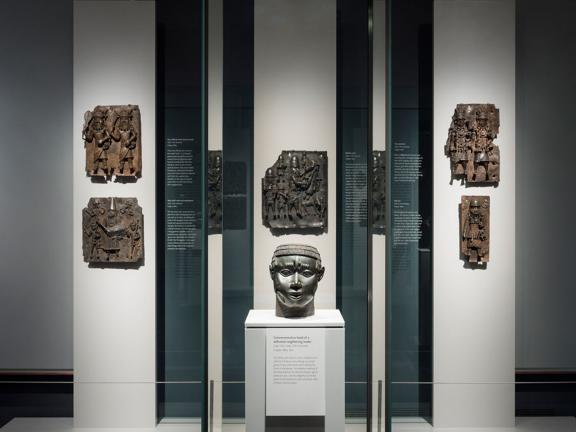 View of Benin gallery, with bronze plaques in background, bronze head in foreground