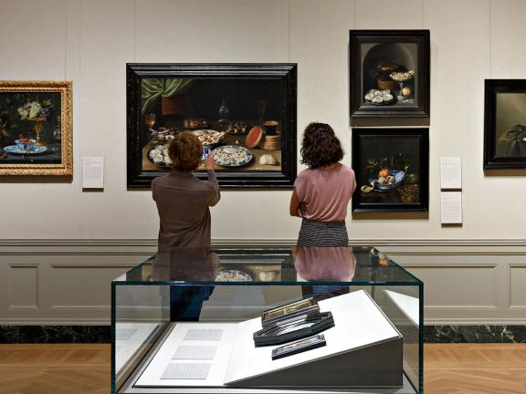 "Two visitors looking at paintings in ""Masterpieces of Dutch and Flemish Painting"" installation"