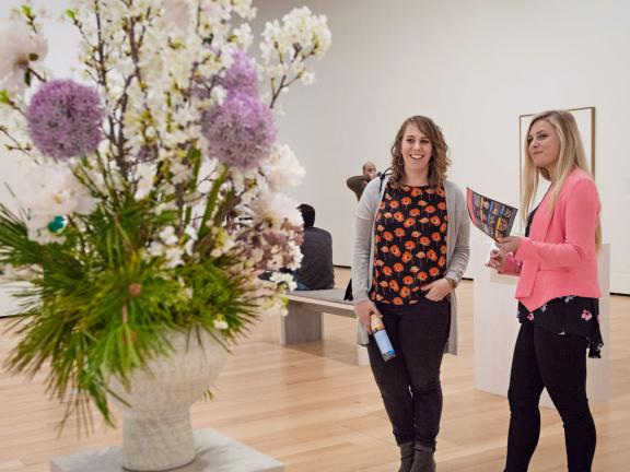 Two visitors looking at floral arangement on pedestal in Linde Family Wing gallery