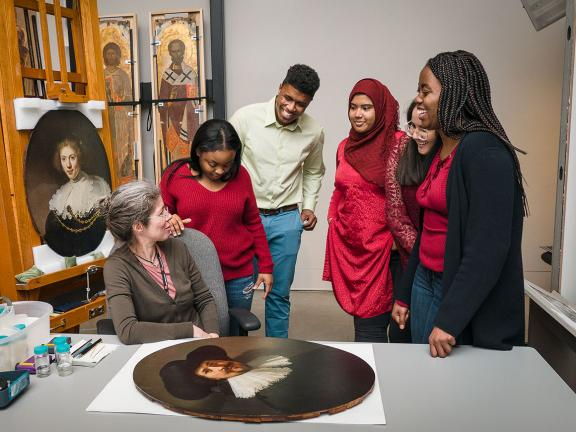 Members of the STEAM Team speak with conservator Rhona MacBeth, sitting next to oval painting on table