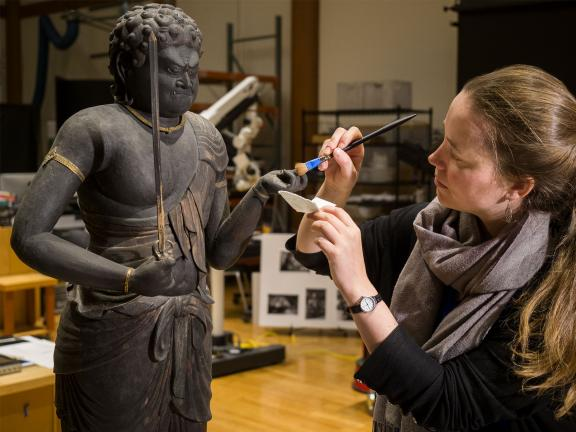 Conservator working on Japanese Buddha sculpture