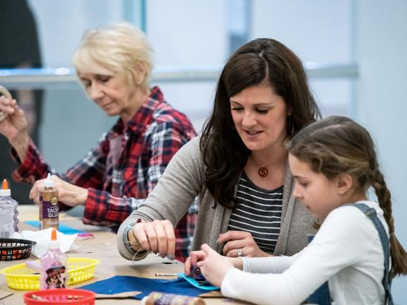 Parent helping child with construction paper for activity at art making table