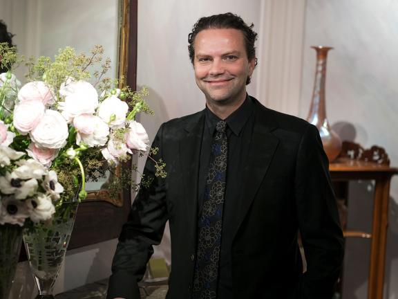 Remco van Vliet in dark suit standing by floral arrangement in glass vase