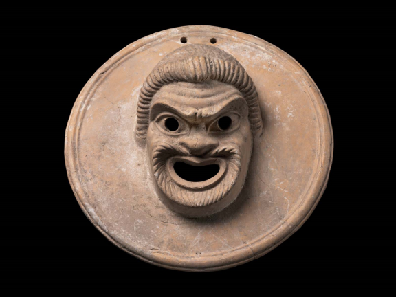 Greek Terracotta suspension disk with an image of a comic mask of a slave