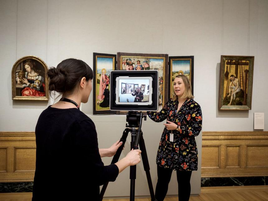 Museum staff member operates camera on tripod livestreaming distance learning program by educator standing in front of triptych
