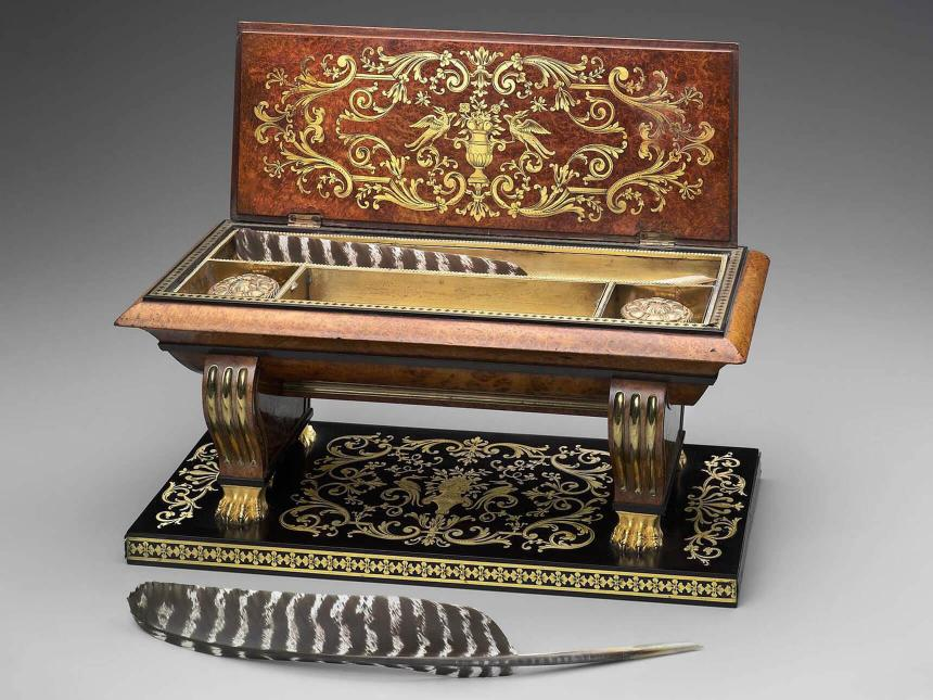 sarcophagus-shaped inkwell with intricate inlaid brass and two quills