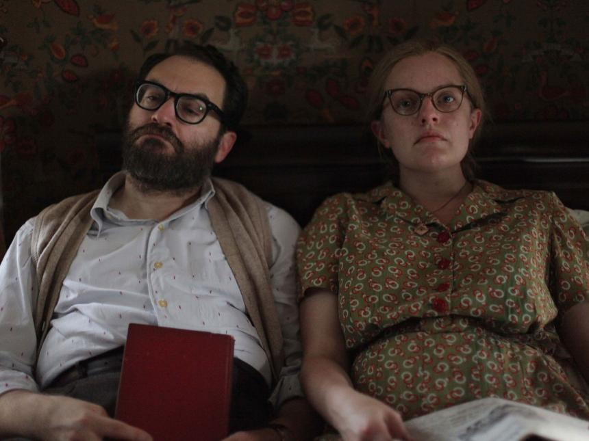 film still from Shirley, depicting couple sitting next to each other on bed