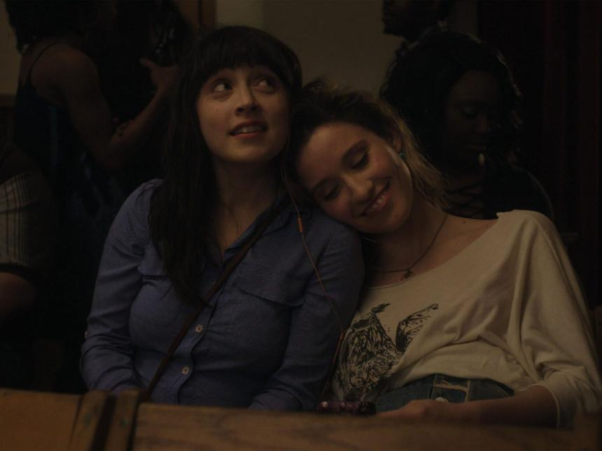 film still from Fourteen, depicting two women sitting next to each other, with one resting her on other's shoulder