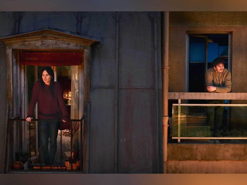 Still from Someone Somewhere, depicting two individuals standing on separate but nearby balconies