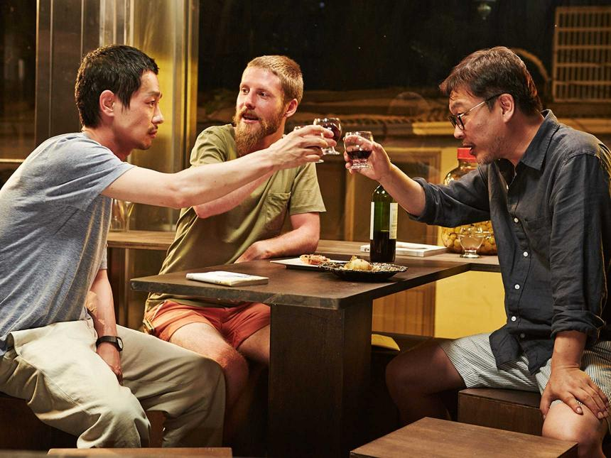 still from film of three men clinking their drinks to cheers around a table