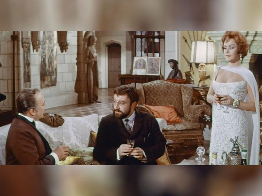 still from film depicting two men sitting on sofa in large room, with woman standing adjacent