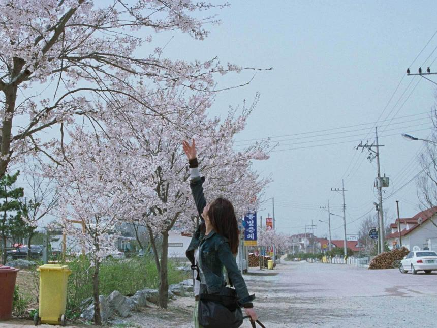 film still depicting woman reaching up towards blossoming tree