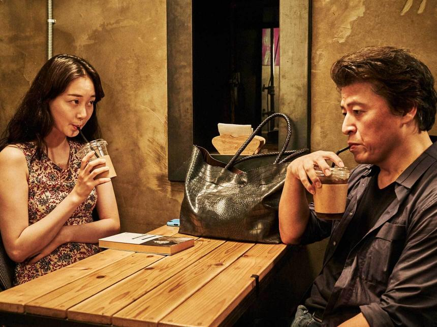 film still depicting two people sitting across table from each other, sipping on drinks