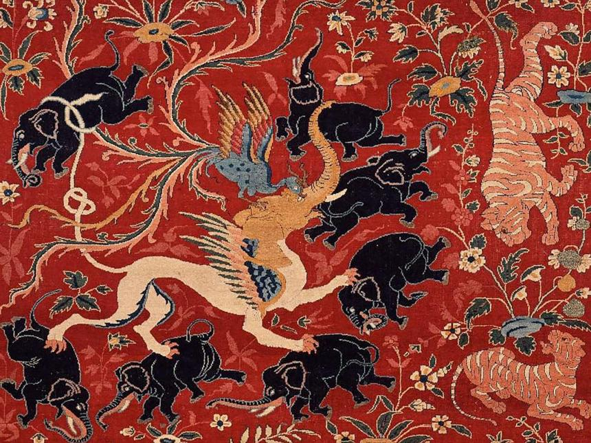 detail of pictorial carpet depicting numerous black elephants and tigers surrounding phoenix and an elephant-headed chimera-like creature