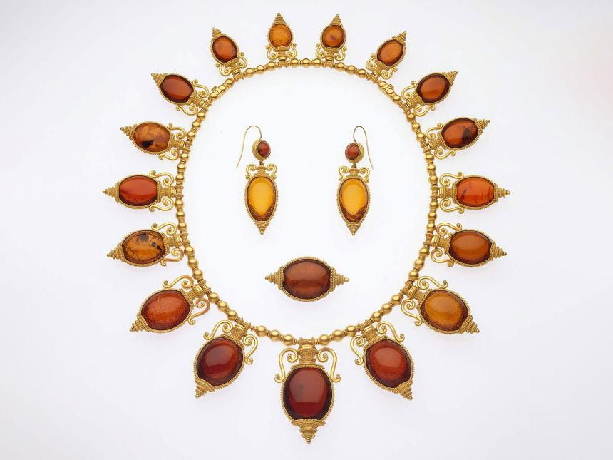 arrangement of necklace, earrings, and a ring that are made with an amber colored stone