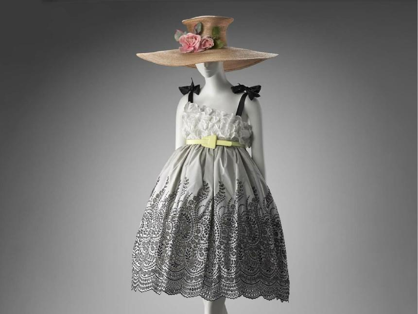 mannequin modeling evening dress with intricate gray pattern on skirt, black bows on shoulder strap, topped off with large straw hat