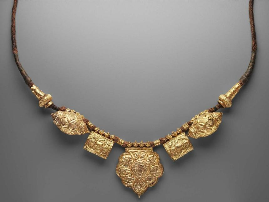 gold necklace with several pendants on a brown cord