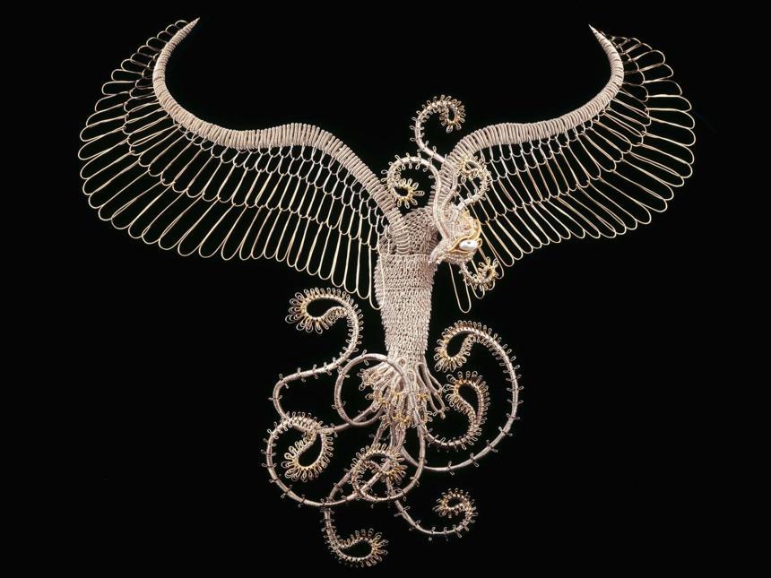 big silver neckpiece sculpted like a flying bird