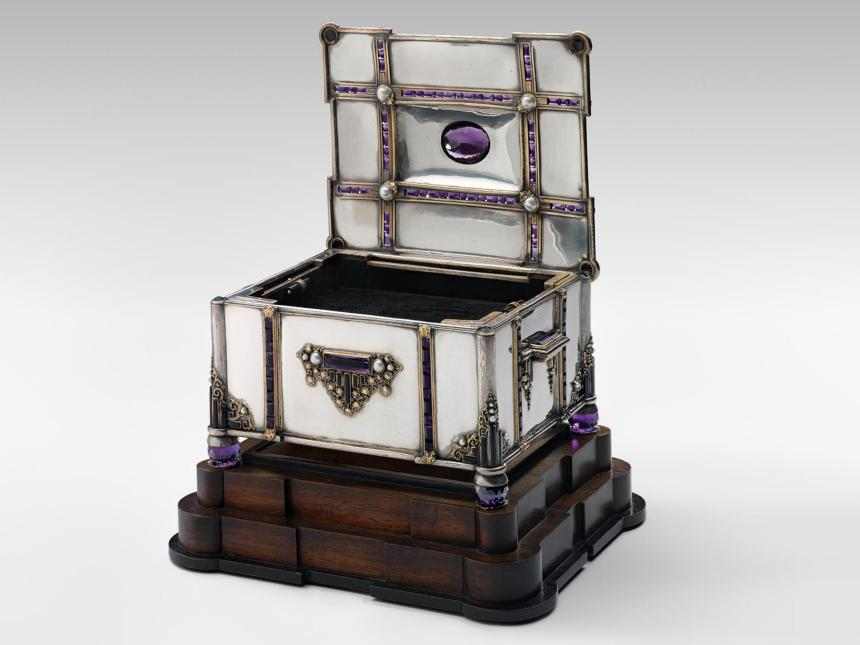 silver box with inlaid jewels on a dark wood base