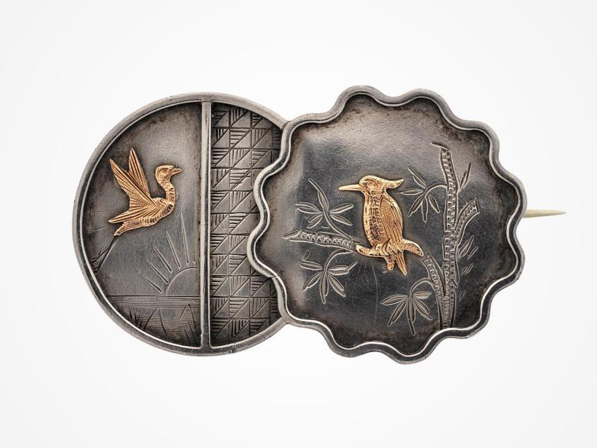silver brooch with two gold birds on it