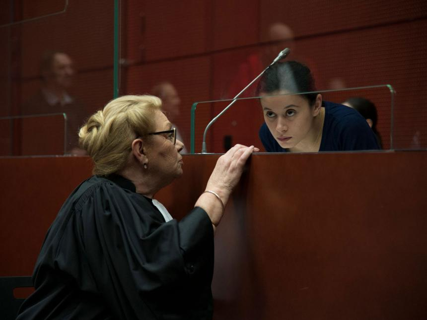 Still from The Girl with a Bracelet, depicting woman talking to lawyer in courtroom behind plexiglas barrier