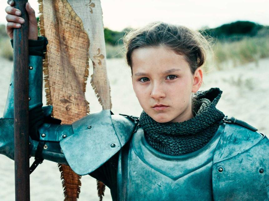Still from Joan of Arc, depicting young woman in armor holding flag