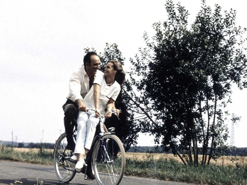 Still from The Things of Life, depicting man riding on bicycle with woman seated in front of him