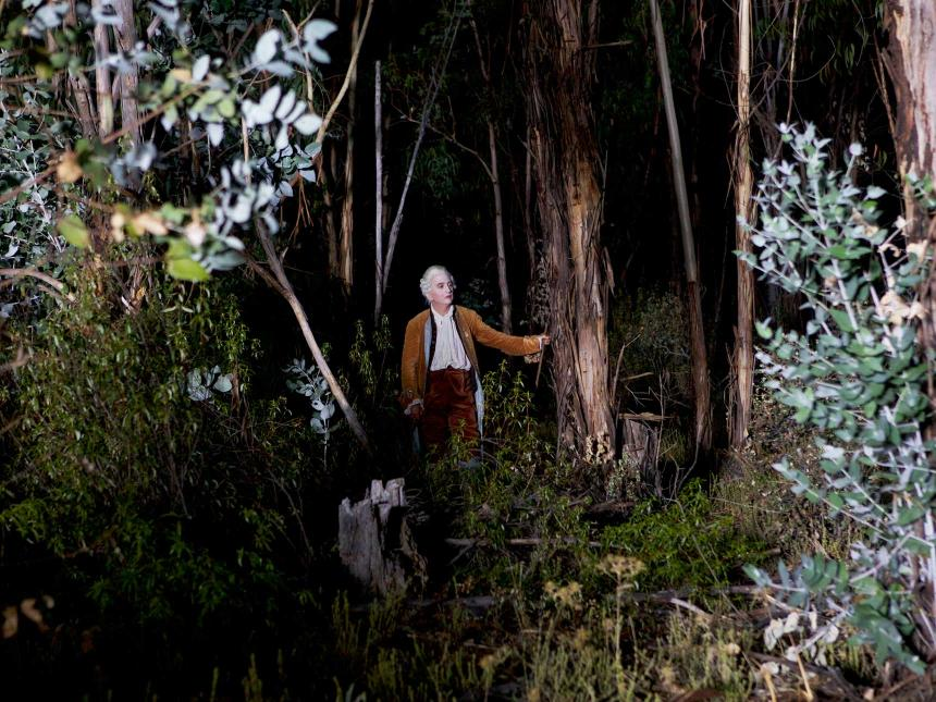 Still from Liberté, depicting man in powdered wig standing in forest