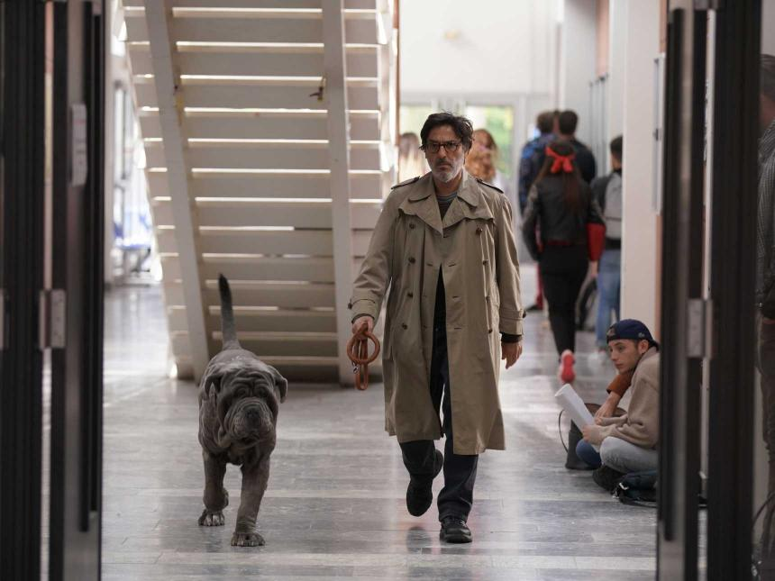 Still from My Dog Stupid, depicting man in trench coat walking next to dog down hallway