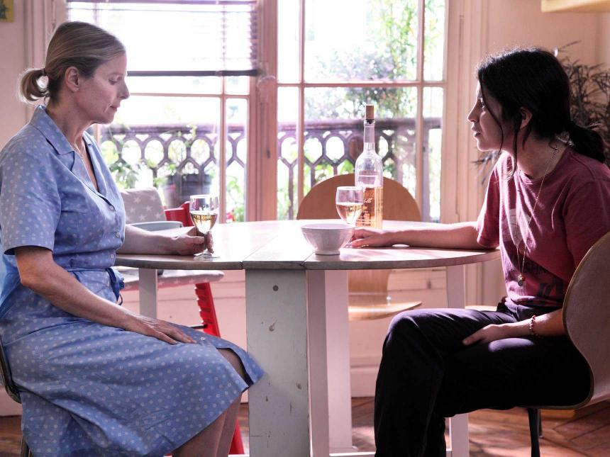 Still from The Perfect Nanny, depicting young woman sitting on opposite side of table from older nanny