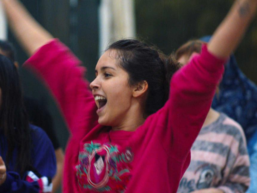 Still from Papicha, depicting girl in hot pink shirt cheering with hands in the air