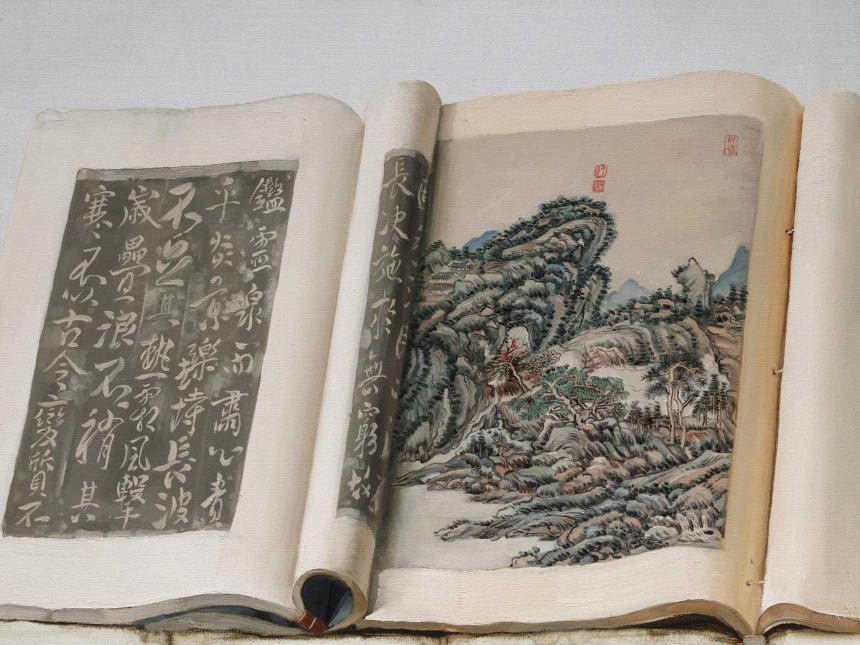 book open to page with Chinese characters and another depicting mountain landscape