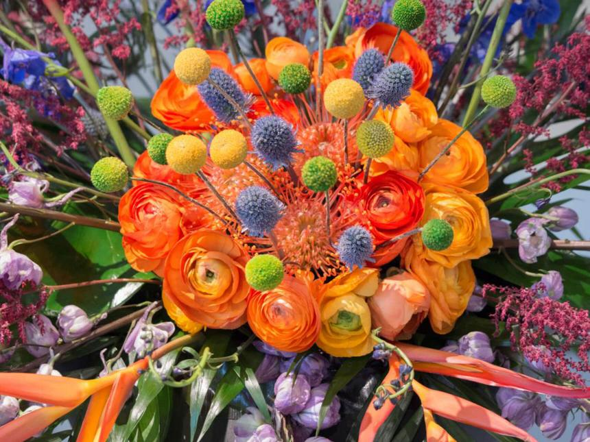 Detail of brightly colored floral arrangement with large orange bloom in the center surrounded by smaller purple and yellow poms