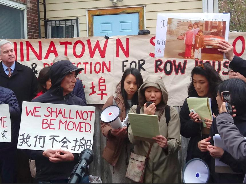 Film still from A Tale of Three Chinatowns, depicting a housing protest in which a crowd of people holding signs and banners are listening to a speaker